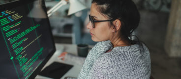 A woman wearing a grey sweater looks intently at a computer screen with lines of code.
