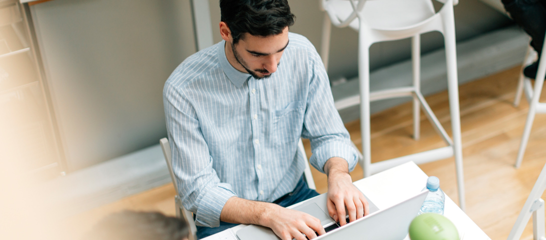 Downward view of a man in a collared blue and white striped shirt typing on a laptop.