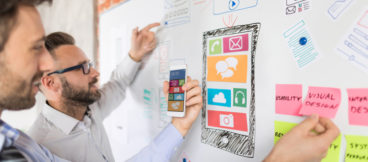 Two men stand at a white board with doodles of cellphone home screens discussing visual design and usability.