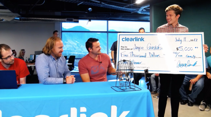 Three Clearlink employees sit at a table smiling and looking at another man holding a large check made out for $5,000.