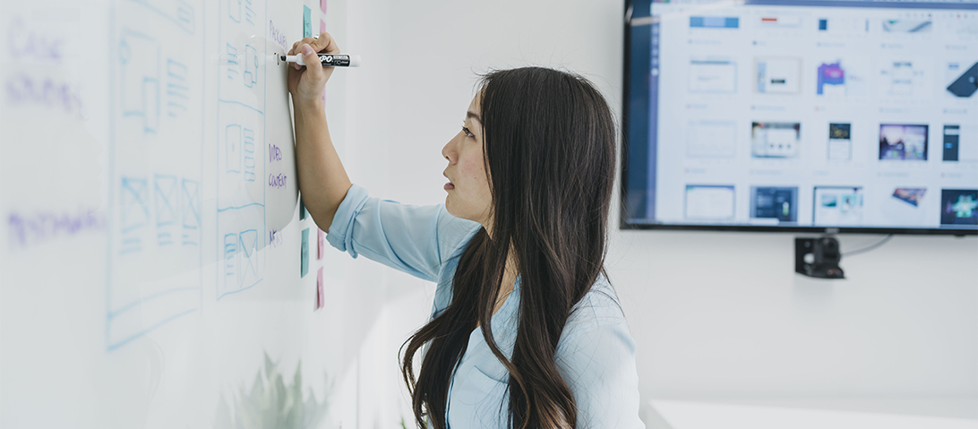 A woman charts a user experience journey on a white board.