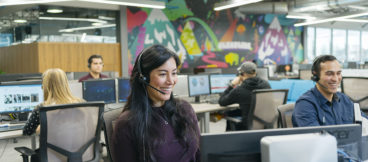 Sales agents in a call center chat with customers on headsets