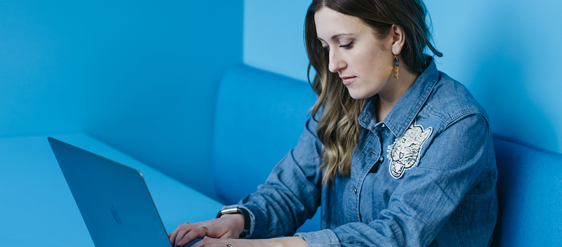 A woman wearing a blue denim shirt works on a laptop in a blue booth with blue walls