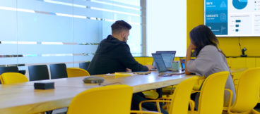 Two people looking at their laptops sit in a conference room with bright yellow chairs.