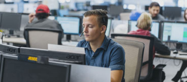 A sales agent sits at a computer with a headset on.