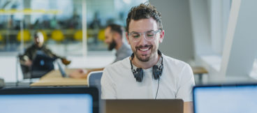 A smiling person with headphones around their neck sits at a desk, looking at their computer screen with a smile on their face.