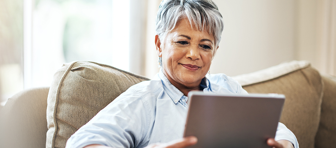 A woman with short gray hair sitting on a couch holding her tablet and smiling.
