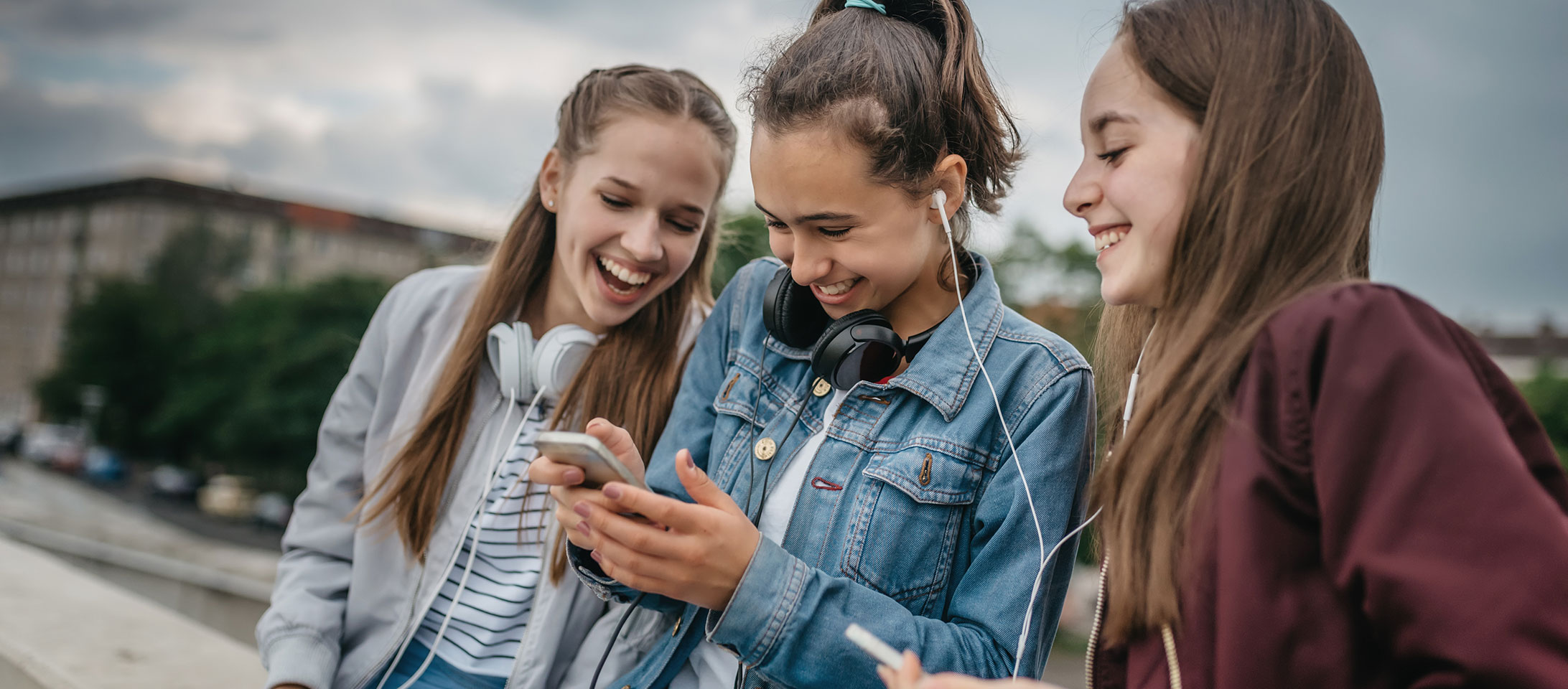 Teen girls looking at smartphones and laughing