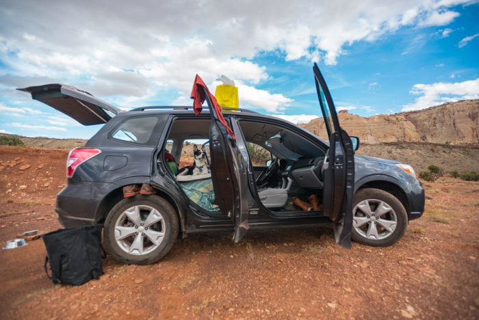 Subaru hatchback with all the doors open parked on red dirt with a dog in the back seat.